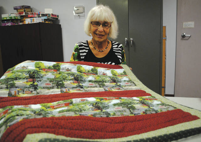 "Janet Reuwer created a full-sized Coca-Cola quilt two weeks ago because it is ""nostalgic"" and ""makes her feel good,"" she said. Reuwer creates quilts that she said she later gives away to local nursing homes."