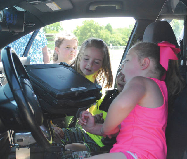 Students explored the interior of a bus, fire trucks and police vehicles. They are pictured as they saw the interior of a Fairborn police car.