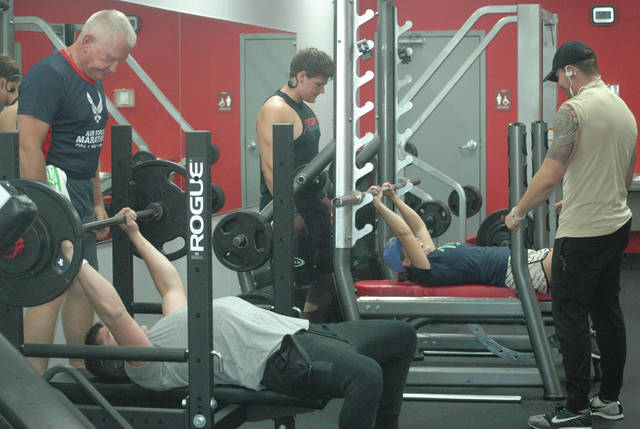 Scott Halasz | Xenia Daily Gazette Corey Jackowski, owner of Xenia's Snap Fitness (right) watches as some members lift weights.