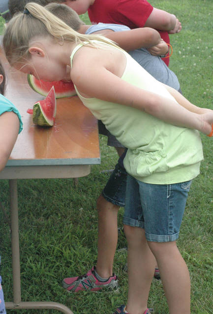 Scott Halasz | Greene County News Breanna Coates, 8, chomps away at the watermelon during the 8-11 age group. She finished second.