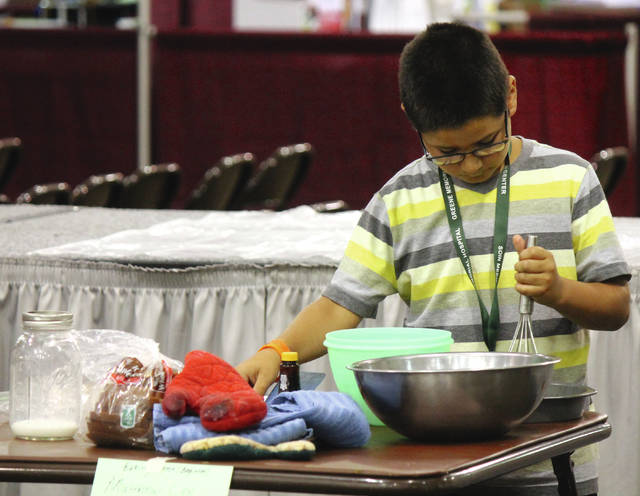 Anna Bolton   Greene County News Matthew Lee, 9, makes french toast during the beginners' division of the baking contest July 31.