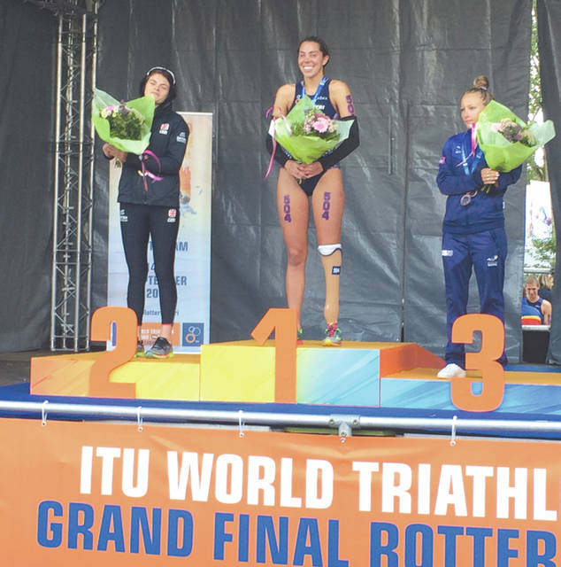 Cedarville University sophomore Grace Norman, of Jamestown, stands atop the awards podium after winning the women's PTS5 world paratriathlon championship with a win Friday, Sept. 15 in the International Triathlon Union-sanctioned World Triathlon Series event in Rotterdam, The Netherlands.