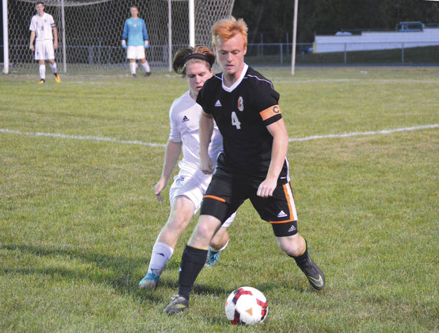 Beavercreek senior co-captain Ryan Bernt (4) gathers control of the ball, as Fairborn sophomore midfielder Keegan Dierker defends, during Tuesday night's Oct. 3 high school boys soccer match at Fairborn High School.