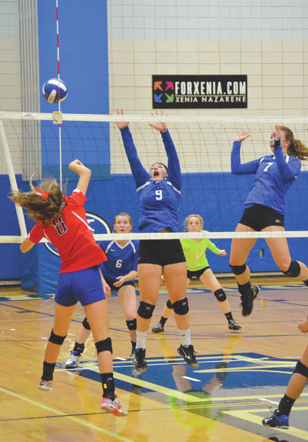 Carroll's Sophia Carter hits a shot down the left line past Xenia's Megan Brewer (9) and Heidi Alex (7) as Skylar Throop (6) and Grace Brown (14) follow the action from the back court, during Wednesday's Oct. 4 girls high school volleyball match at Xenia High School.