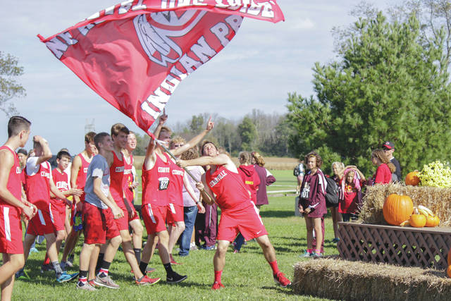Members of the Cedarville High School boys cross country team wave their team flag with pride as they head to the awards platform to accept their championship, Oct. 14 at Cedarville University.