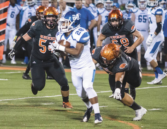 Miamisburg running back Zion Lewis (28) tries to avoid the defensive rush of Beavercreek defensive lineman Noah Koenig (54), nose tackle Stevie Llanas (front) and defensive end Reece Blackmore (69) during Friday's 21-0 Beavercreek win at Frank Zink Field.