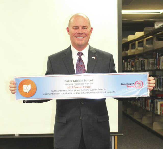 Linda Collins | Fairborn Herald Baker Middle School Principal Brad Holt proudly displays replica of PBIS Bronze Level Award banner.