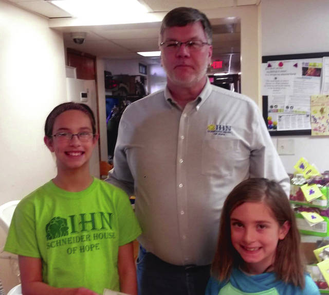 Submitted photo Autumn and Alayna Allport presented funds from the 2016 cookie jar fundraiser to IHN director William Mallernee last year. The girls organized the cookie jar fundraiser again this holiday season.