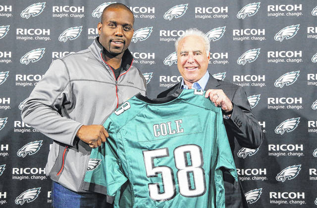 Photo courtesy Philadelphia Eagles Xenia native Trent Cole signed a ceremonial contract with the Philadelphia Eagles prior to their game with the Oakland Raiders Dec. 25 so he could retire from the NFL as a member of the Eagles. He played most of his pro career with Philadelphia, before spending the last two seasons with the Indianapolis Colts. Cole is pictured with Eagles owner Jeffrey Lurie.