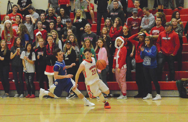 Cedarville's Colby Cross (23) backtracks after a loose ball, in front of a festive Cedarville student section, Friday Dec. 22 in the first half of an Ohio Heritage Conference game with Greeneview. Cross led Cedarville with 23 points scored in a loss to the Rams.