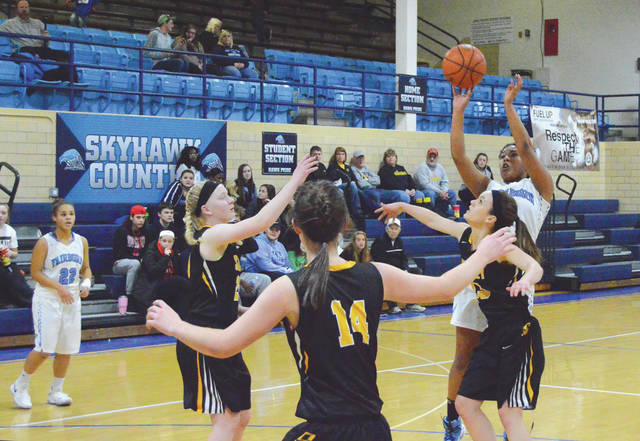 Khala Powell puts up a shot against a swarm of Sidney Yellow Jackets, during the first half of Wednesday's Jan. 17 girls high school basketball game in Fairborn. Powell scored a team-best eight points in the fourth quarter to help lead Fairborn to a 47-40 win.