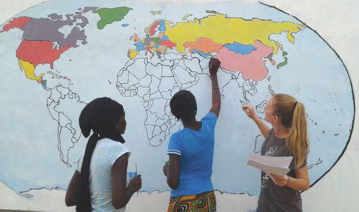 Jacquelyn Weaver worked with schoolchildren to paint a world map mural on the side of the village schoolhouse.