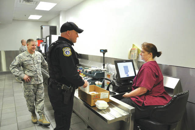 """Submitted photo Nancy Williams, Pitsenbarger Dining Facility cashier, rings up Officer Ryan Gray's main entrée """"to go"""" while Chief Master Sgt. Thomas Christopher looks on at the Pitsenbarger Dining Facility located in Building 1214, Area A, Kittyhawk."""