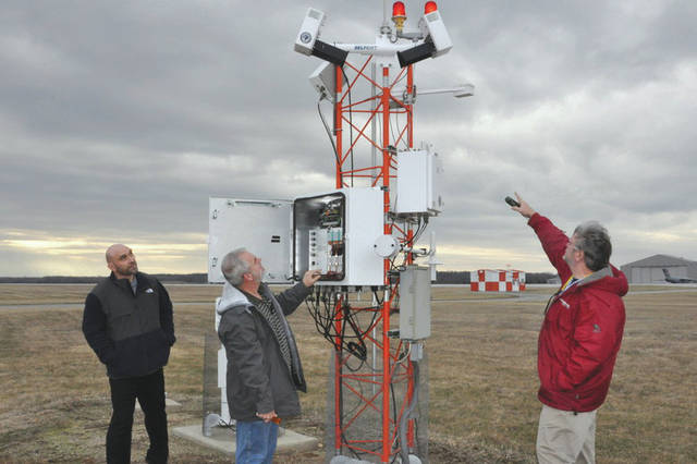 Submitted photo From left: Meteorologist Scott Lutz, Electronics Technician Marvin Mullins and Forecaster Brent Sullins, all personnel assigned to the 88th Operations Support Squadron who keep the Weather Station up and running, discuss the capabilities of the FMQ19, an automated weather observing system located on the base flight line.