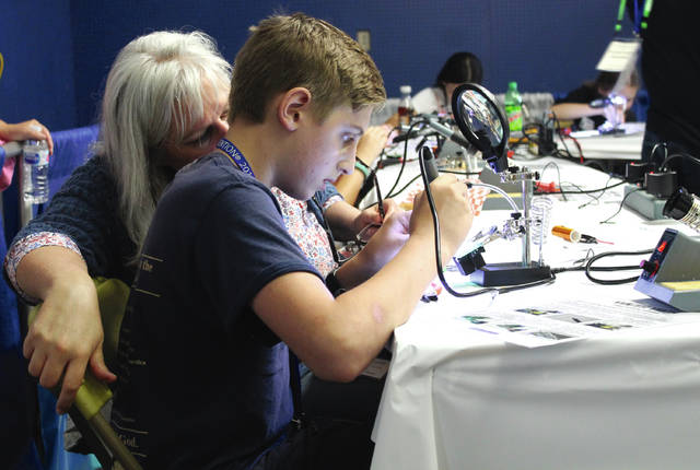 Anna Bolton   Greene County News Allison Mackey watches as her son Isaiah Mackey from Hanover, Indiana practices soddering in the Youth Tech area of Hamvention May 18. Isaiah's dad is a licensed amateur radio operator; this was their family's first time at Hamvention.