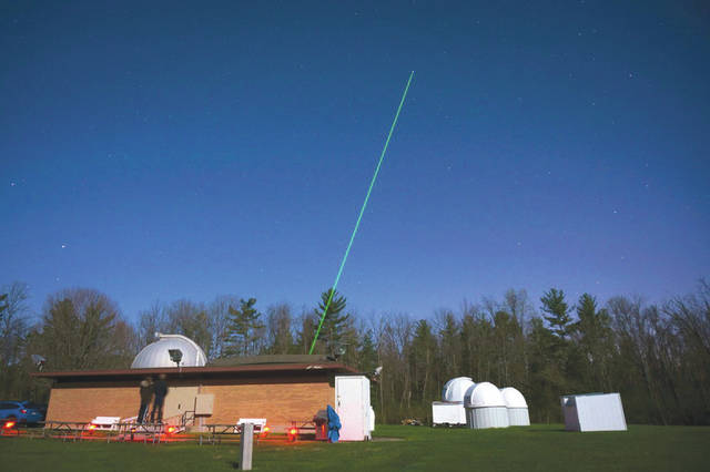 Submitted photo The Turbulence and Aerosol Research Dynamic Interrogation System, or TARDIS, laser is fired into the night sky above the John Bryan State Park observatory.