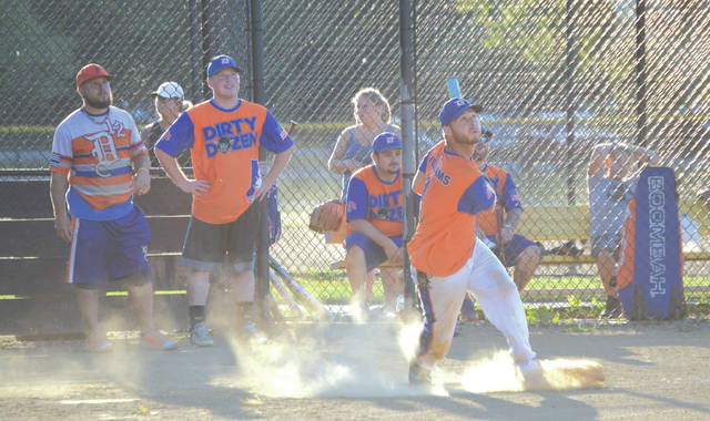 The players' eyes are all on the ball as a member of the Dirty Dozen team smacks an inside-the-park home run Friday, July 6 at Rotary Park in Beavercreek.