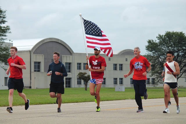 Anna Bolton | Greene County News Wright-Patterson Air Force Base military personnel, civilian employees and their families run to the finish line Sept. 11 during the annual Run for the Fallen on base. At the finish, participants received American flag dog tags.