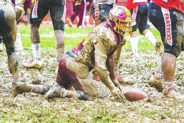 An unidentified muddy Marauder tries to get onto his feet and out of the midfield slop, during the rainy first half of Saturday's Sept. 7 college football game between host Central State and visiting Clark Atlanta, at McPherson Stadium in Wilberforce.